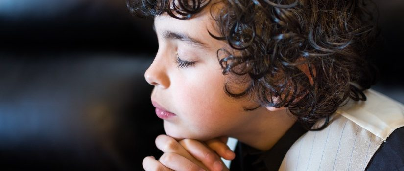 Child praying and praising God.